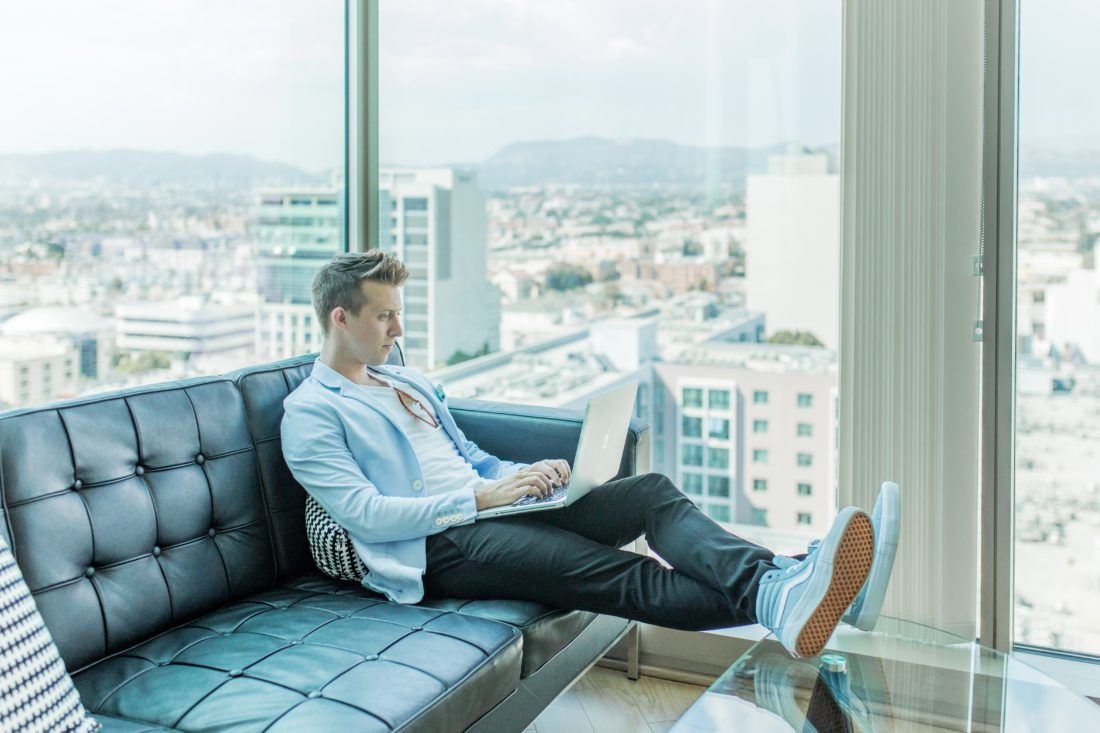 passive income for designers - designer sitting on couch in city